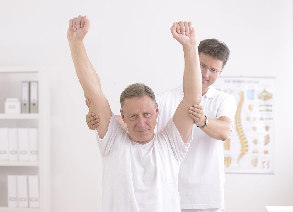 Chiropractor helping patient relieve his joint pain by properly stretching his arms over the top of his head