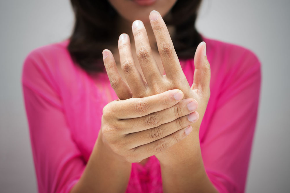 Woman experiencing hand pain should seek chiropractic treatment